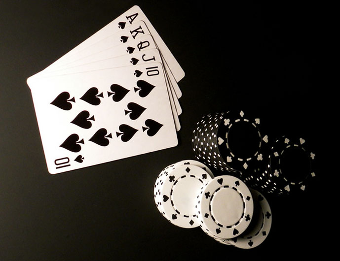 Playing cards laying next to casino chips